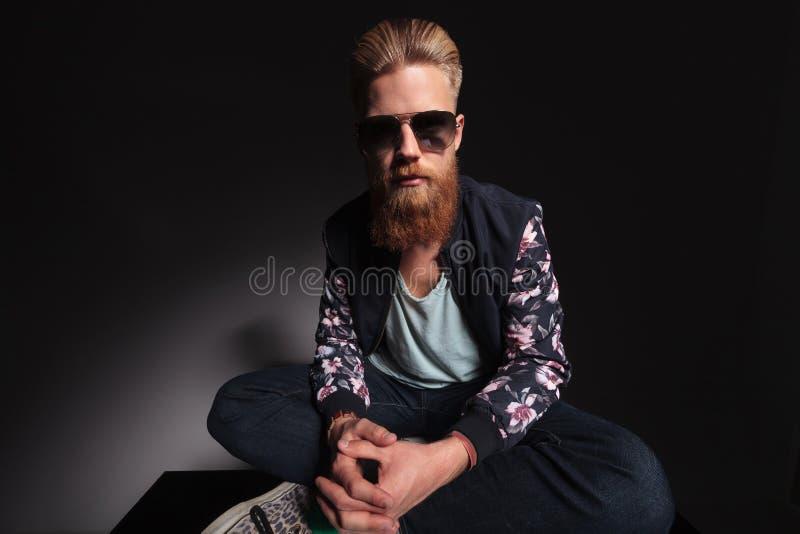 Homme barbu avec les pieds croisés images libres de droits