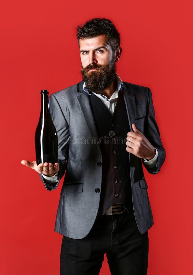 Homme barbu avec un champagne de bouteille de et un verre Mâle élégant dans le smoking, costume, veste Bouteille de participation photographie stock libre de droits