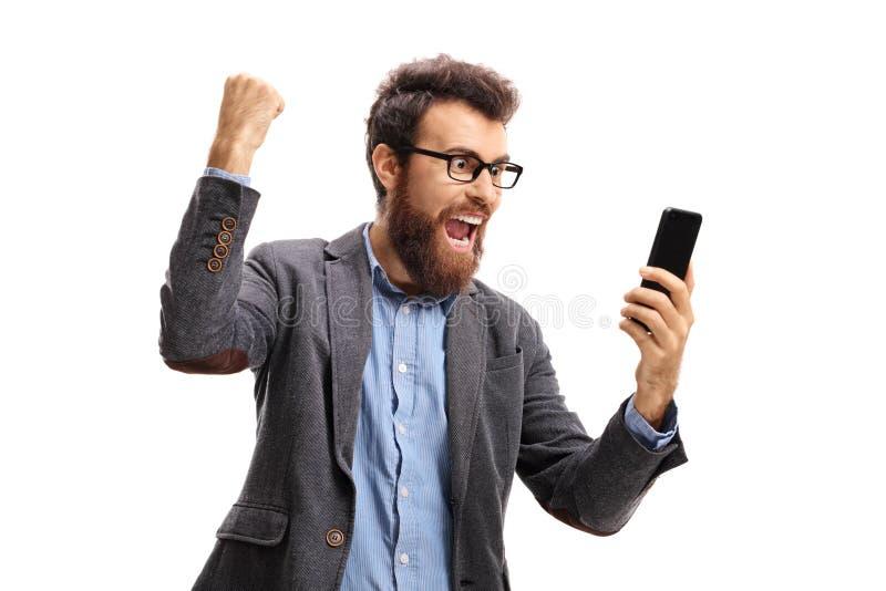 Homme barbu avec un téléphone faisant des gestes le bonheur photo libre de droits
