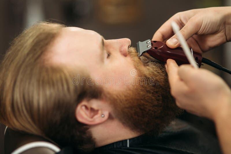 Homme barbu ayant une coupe de cheveux avec des tondeuses image libre de droits