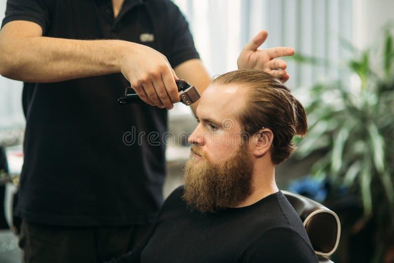 Homme barbu ayant une coupe de cheveux avec des tondeuses photo stock