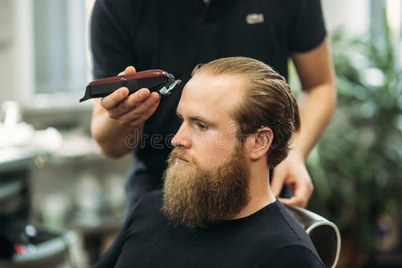 Homme barbu ayant une coupe de cheveux avec des tondeuses photos stock