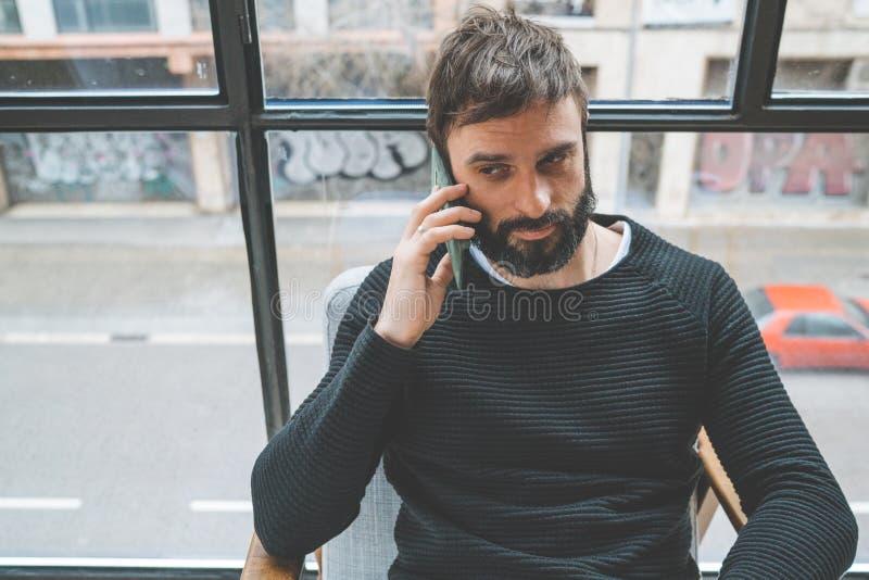 Homme barbu bel à l'aide de son smartphone pour faire l'appel à la maison moderne Fond brouillé horizontal photographie stock libre de droits