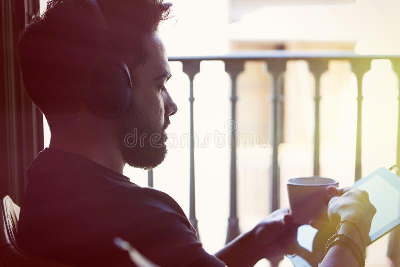 Homme barbu bel dans des écouteurs écoutant la musique sur le comprimé électronique à la maison Temps occasionnel de détente et d image libre de droits