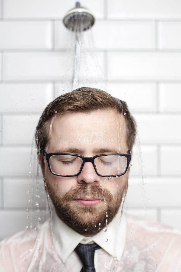 Homme barbu bel dans les verres, la chemise et les supports de lien dans la salle de bains sous l'eau chaude qui vient de la boît images libres de droits