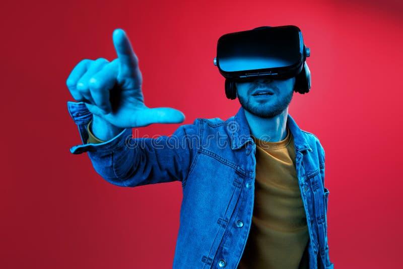 Homme barbu bel essayant le casque de VR et explorant un autre monde dans le studio sur le fond rouge dans la lampe au néon Smart image stock