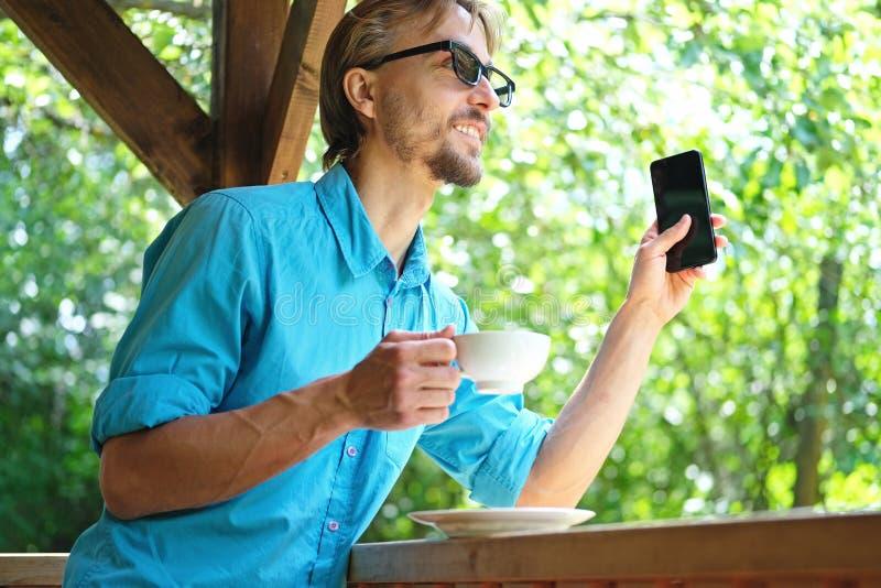 Homme barbu bel la tenue de détente avec les verres et le smartphone en son café potable de main et en saluant quelqu'un en été o images stock