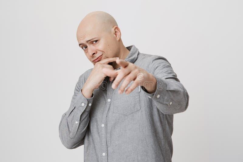 Homme barbu bel tenant une main sur le menton et vérifiant quelque chose, se dirigeant à l'appareil-photo au-dessus du fond blanc image libre de droits
