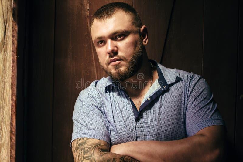 Homme barbu brutal avec un tatouage sur son bras, un portrait d'un homme dans la lumière dramatique contre un mur en bois brun, b photographie stock