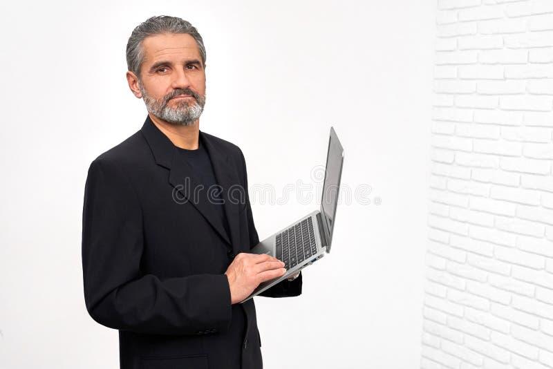 Homme barbu dans l'ordinateur portable noir de participation d'équipement photo libre de droits