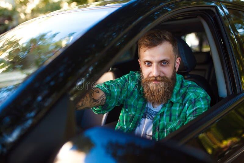 Homme barbu dans la voiture Jeune homme conduisant sa voiture images stock