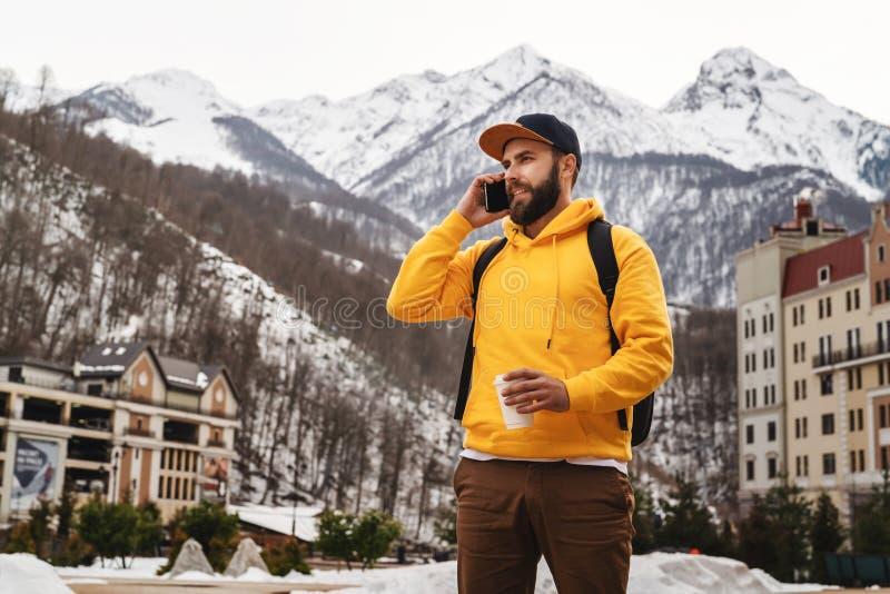 Homme barbu dans le hoodie jaune avec des supports de sac à dos sur le fond de hautes montagnes neigeuses, parlant au téléphone p image stock