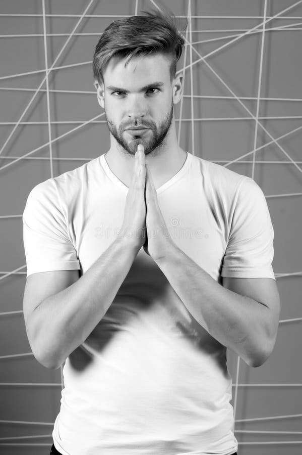 Homme barbu dans le T-shirt blanc avec les mains de prière Macho barbu avec la barbe sur le visage non rasé, noir et blanc photographie stock libre de droits