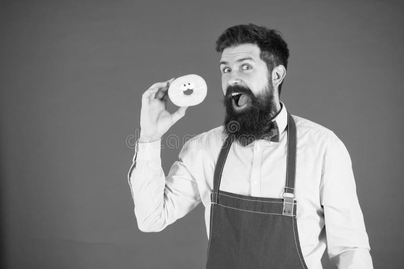 Homme barbu dans le tablier R?gime et nourriture saine R?gime de beignet calorie Faim de sensation Aucun r?gime Homme de chef en  photographie stock libre de droits