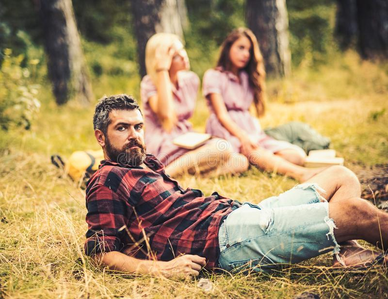 Homme barbu dans le temps de dépense de chemise de bûcheron avec des amis dehors Homme bel se trouvant sur le verre en bois extér photographie stock