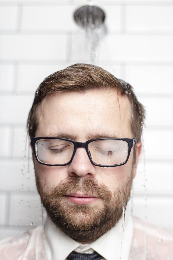 Homme barbu dans les verres, la chemise et les supports de lien dans la salle de bains sous l'eau chaude qui vient de la boîte d' photo libre de droits
