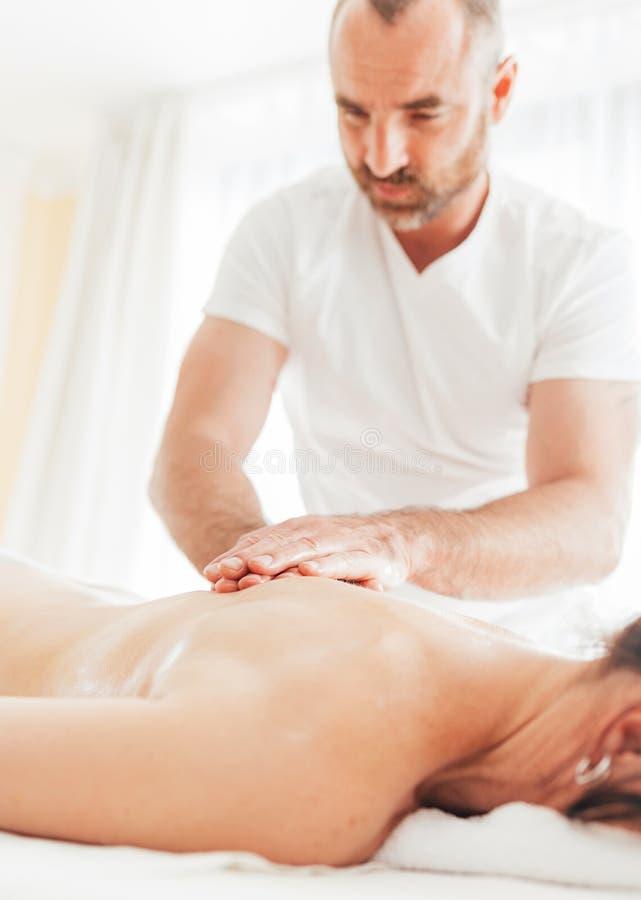 Homme barbu de masseur faisant des manipulations de massage sur la zone de région d'omoplate pendant le jeune massage de corps fé photographie stock libre de droits