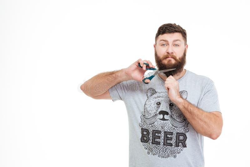 Homme barbu de renversement triste coupant sa barbe avec des ciseaux photographie stock libre de droits