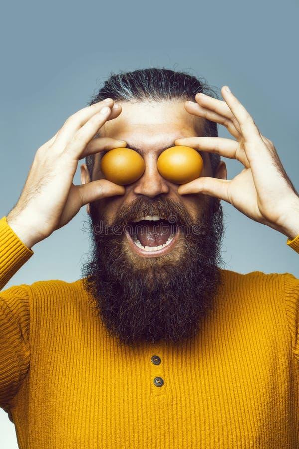 Homme barbu de sourire avec l'oeuf photos stock