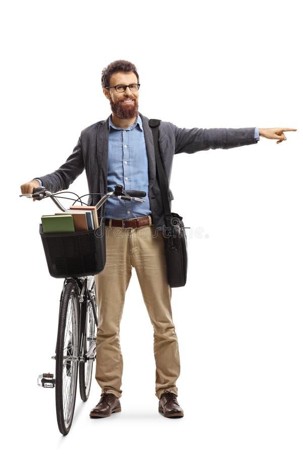 Homme barbu debout à côté de son vélo et pointant vers le côté photographie stock libre de droits