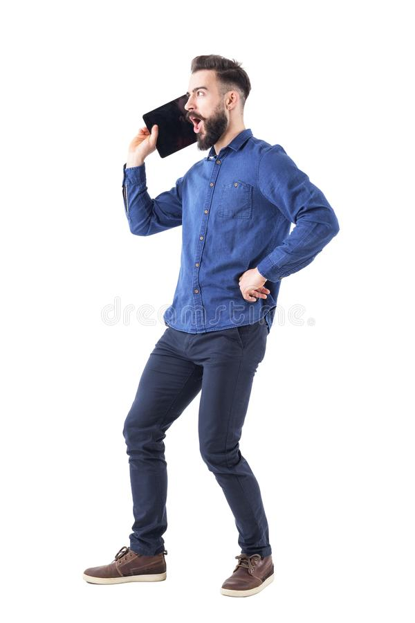Homme barbu drôle d'affaires hurlant sur le grand concept surdimensionné de téléphone portable ou de comprimé photo libre de droits