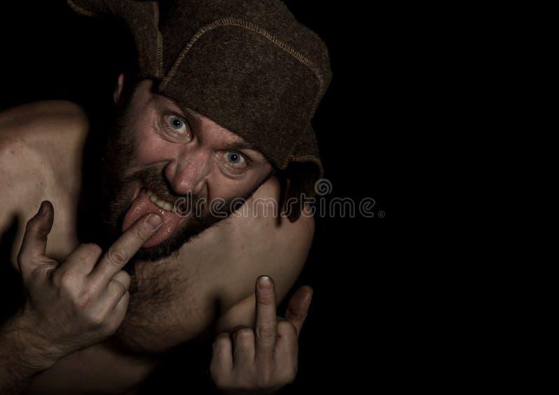 Homme barbu effrayant montrant le doigt moyen homme russe étrange avec un torse nu et un chapeau de laine L'espace libre pour images stock