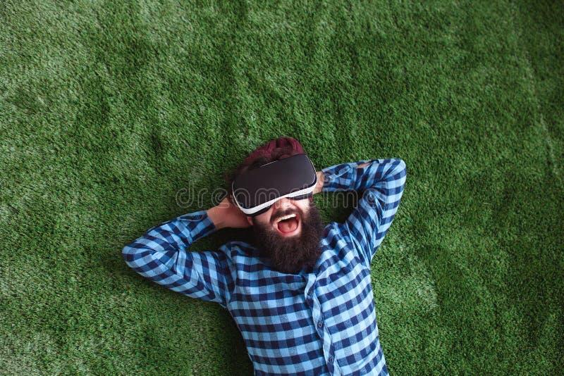 Homme barbu en verres de VR sur l'herbe images stock