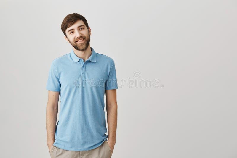 Homme barbu européen attirant amical dans le polo bleu souriant largement tout en se tenant avec des mains dans des poches plus d images stock