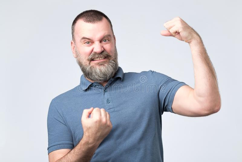 Homme barbu européen de Moyen Âge beau au-dessus de montrer le muscle de bras photo stock
