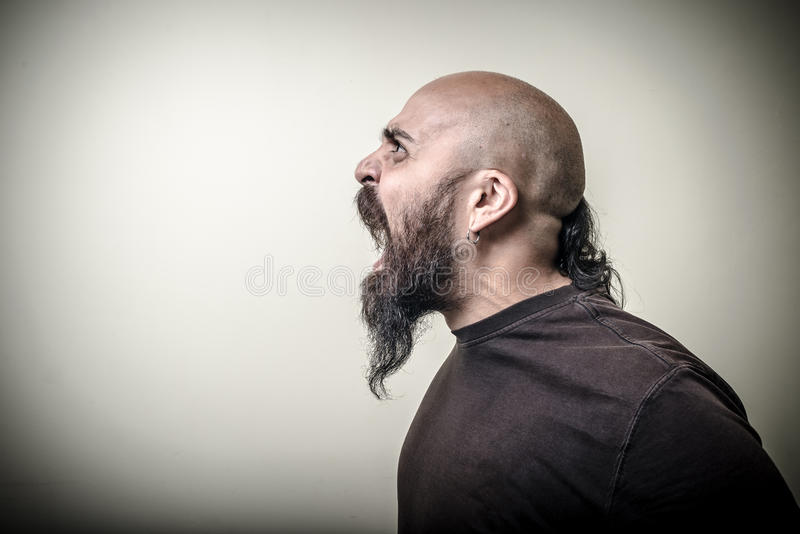 Homme barbu fâché criard de profil photo stock