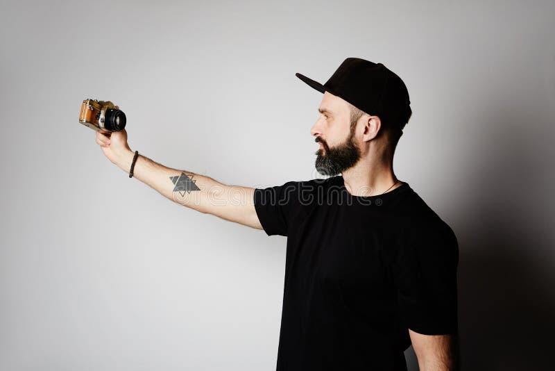 Homme barbu faisant le selfie avec la rétro caméra de photo sur le fond vide photos stock