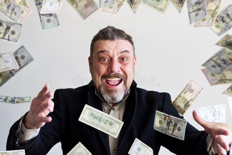 Homme barbu heureux dans un costume, avec des billets d'un dollar tombant autour de lui Réussite finances images stock