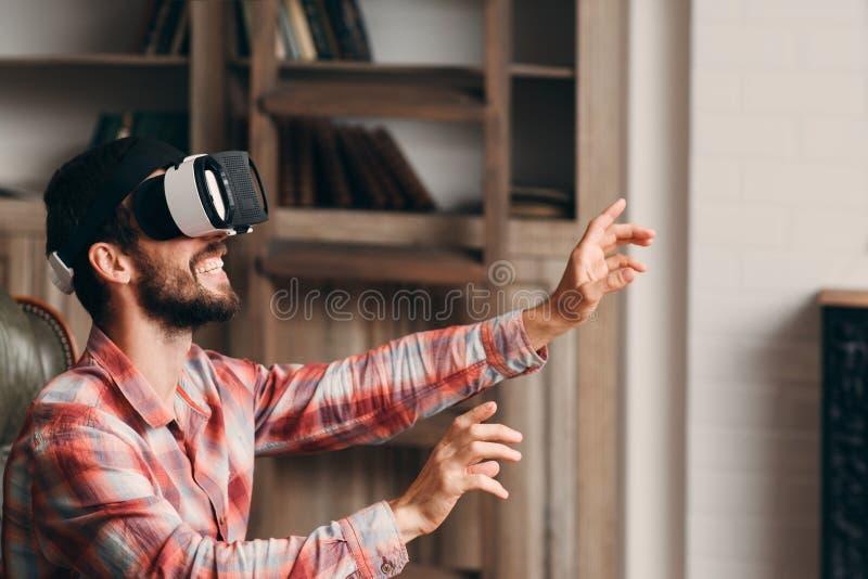 Homme barbu heureux employant des verres de vr photo stock