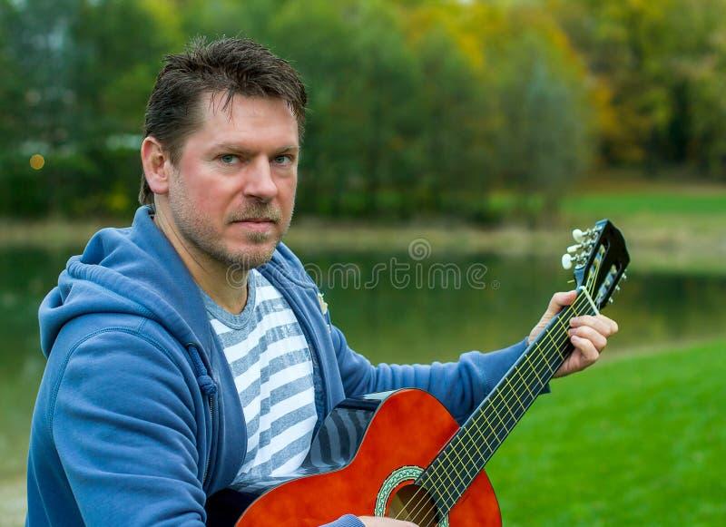 Homme barbu mûr jouant la guitare rouge photographie stock