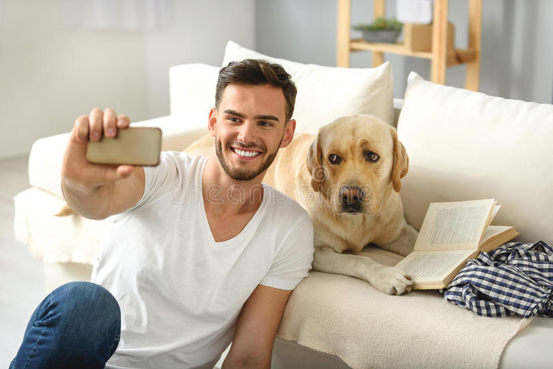 Homme barbu montrant à son chien un téléphone images libres de droits