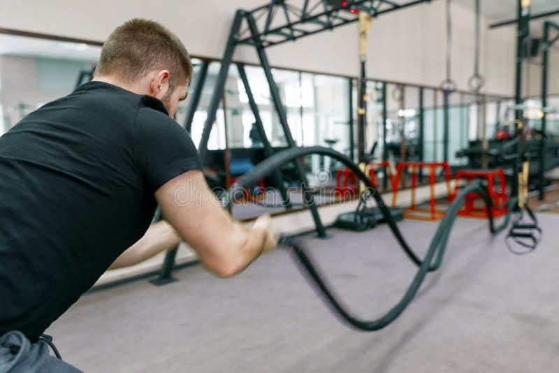 Homme barbu musculaire sportif s'exerçant dans le gymnase avec des cordes de bataille Sport, formation, les gens, concept sain de photo stock