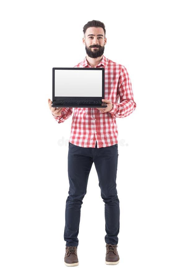 Homme barbu occasionnel futé réussi fier montrant l'écran vide d'ordinateur portable photo stock