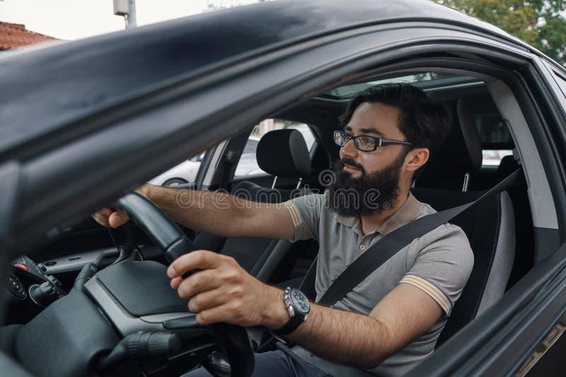 Homme barbu occasionnel moderne conduisant une voiture images libres de droits