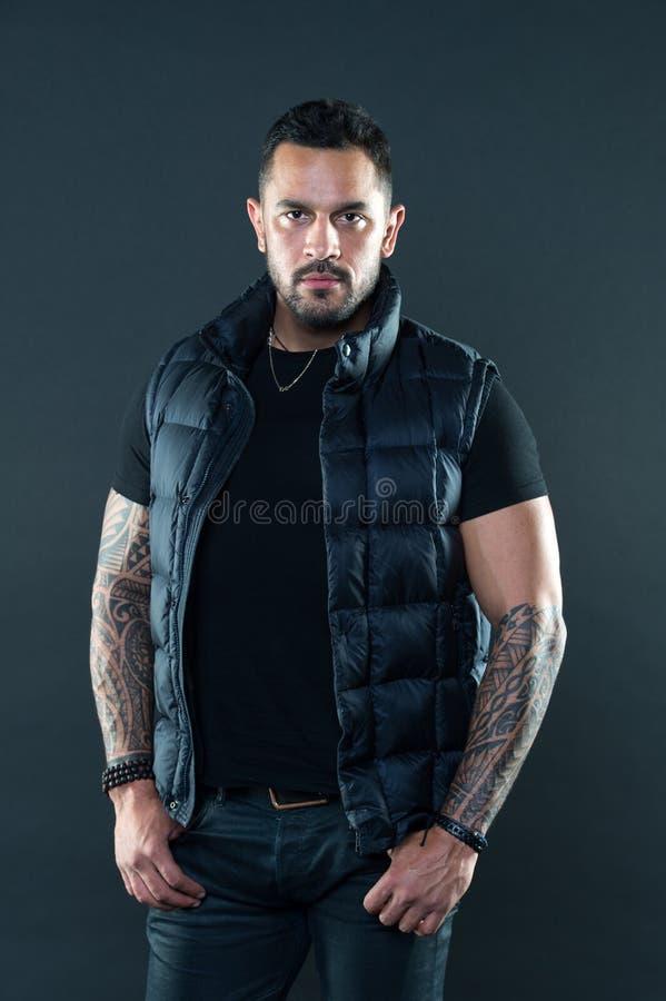 Homme barbu posant avec des tatouages Masculinité brutale non rasée macho de gilet d'usage et concept de mode Tatouez brutal image stock