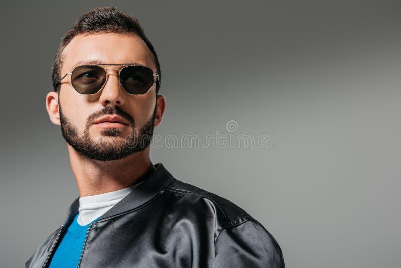 homme barbu posant dans le bombardier et des lunettes de soleil noirs image libre de droits