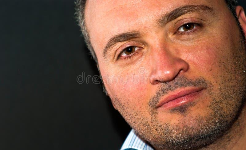 Homme barbu sérieux dans la chemise bleue rayée regardant l'appareil-photo photographie stock