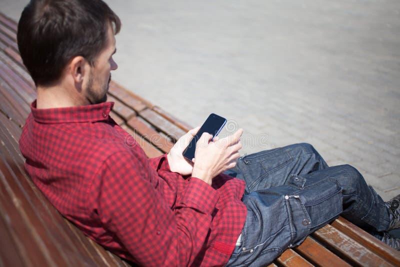 Homme barbu s'asseyant sur le banc en parc avec le t?l?phone dans des mains photo libre de droits