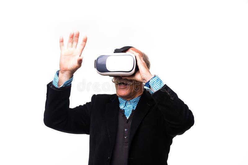 Homme barbu supérieur enthousiaste faisant des gestes et à l'aide du casque de réalité virtuelle, d'isolement sur le blanc photo stock