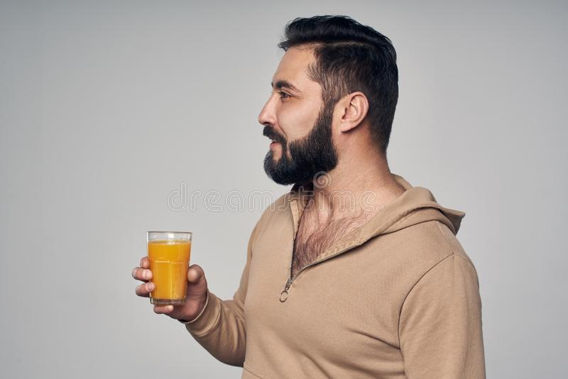 Homme barbu tenant un verre de jus d'orange image stock