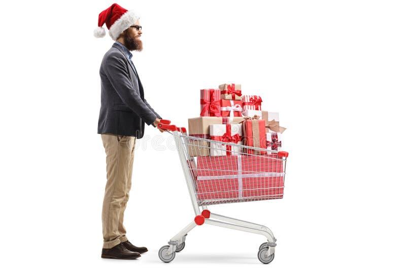 Homme barbu utilisant un chapeau du père noël et se tenant avec un caddie complètement des cadeaux de Noël images stock