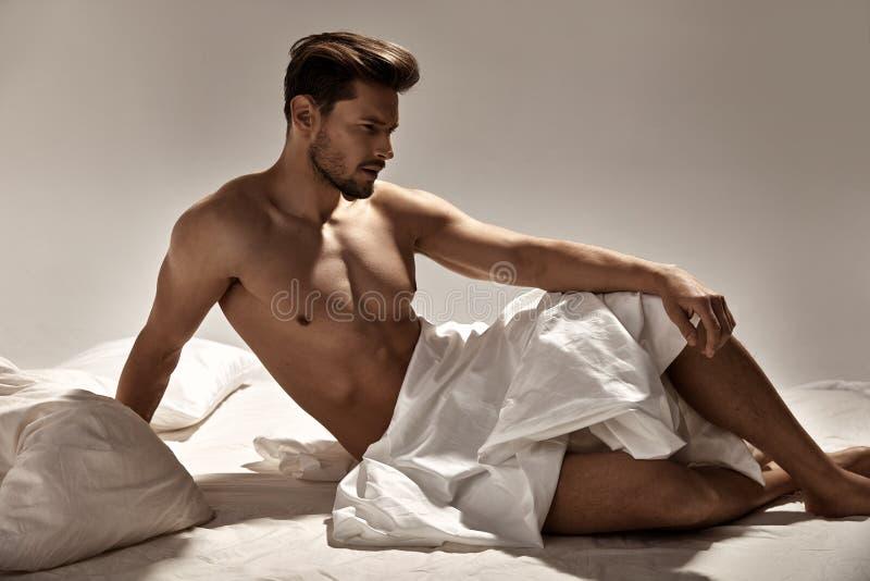 Homme beau et musculaire posant sur le lit mou photos stock