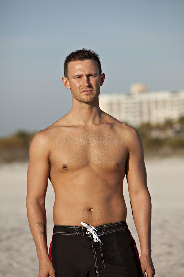 Homme bel à la plage avec le regard sérieux photographie stock libre de droits