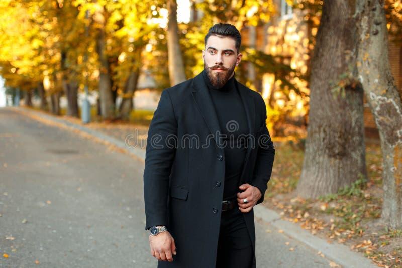 Homme bel élégant dans un manteau noir marchant dehors photographie stock