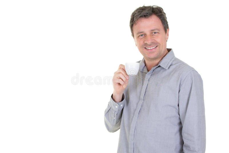 Homme bel agréable dans la chemise bleue buvant tenant une tasse de café et souriant à la caméra tout en posante d'isolement sur  photo stock