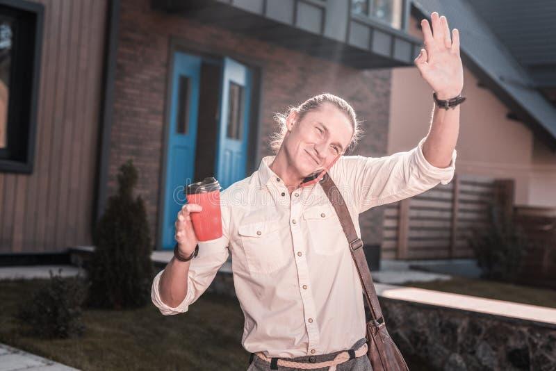 Homme bel agréable saluant son voisin le matin quittant la maison photo libre de droits